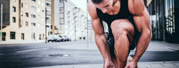A runner bending down to tie his shoe