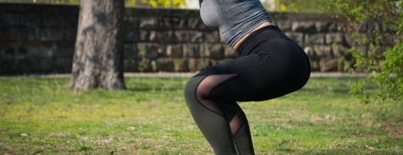 A woman in a park doing a squat
