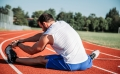 A man stretching on a race track