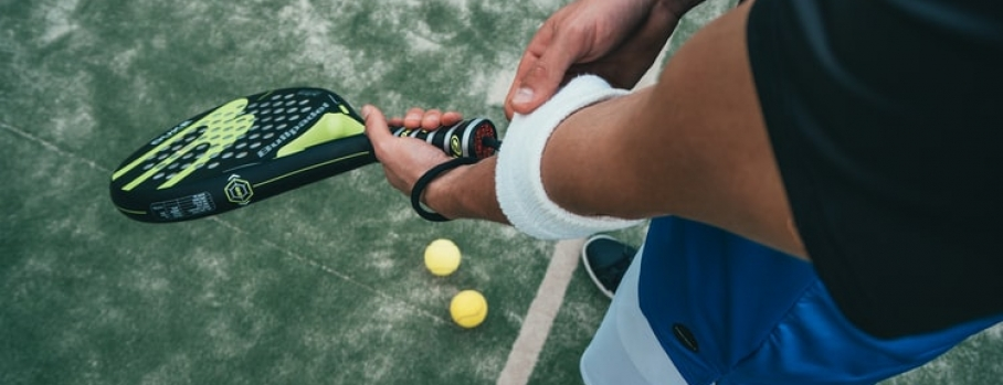 A person holding a tennis racket while adjusting a a wrist band