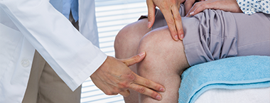 Knee specialist Dr. Warnock in Houston, TX examining a patient's knee