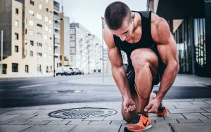 A runner bending down to tie his shoe