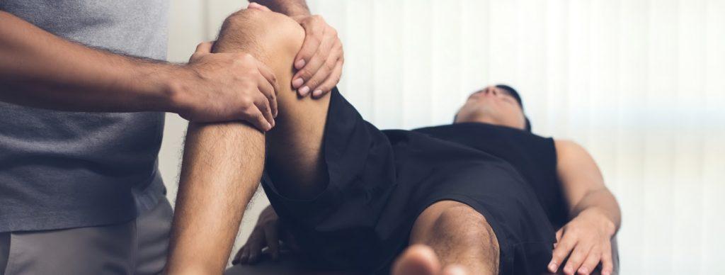 A medical professional massaging a patient's knee