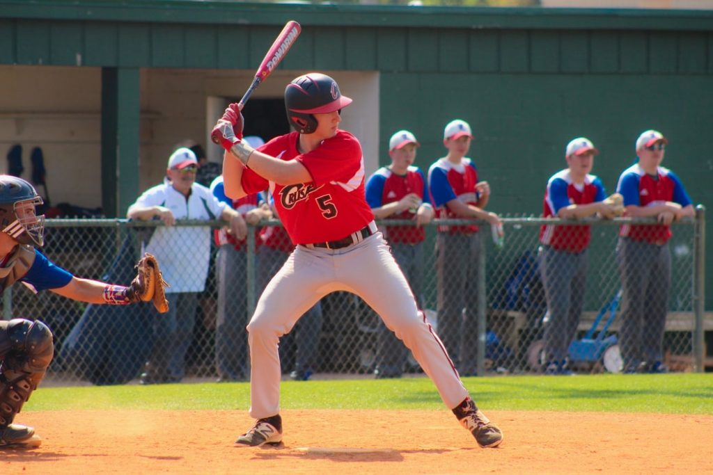 An adolescent stepping up to bat at a baseball game