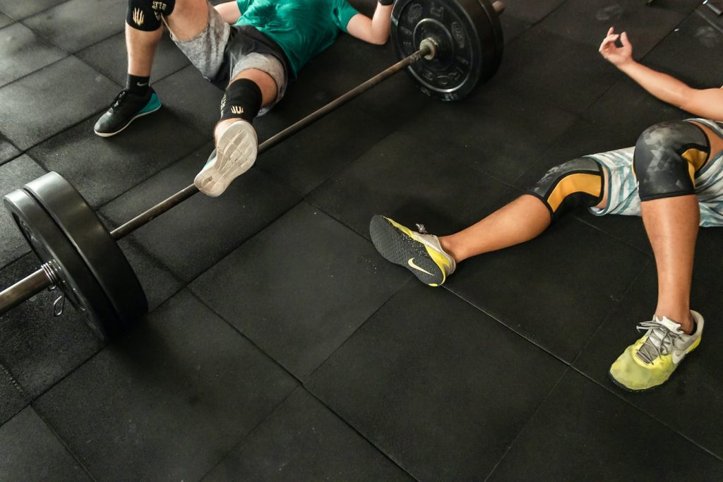 Two people doing knee work outs on a gym floor